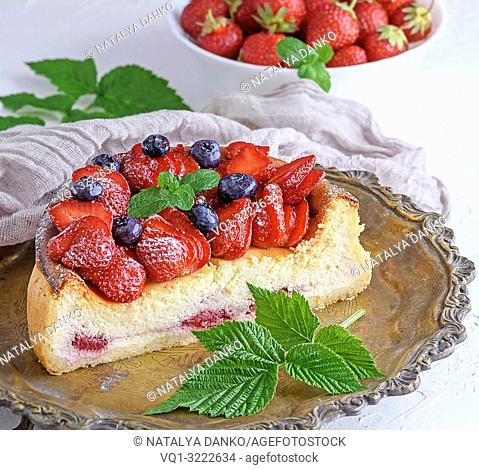 Cheesecake with ripe fresh strawberries on a copper round plate, close up