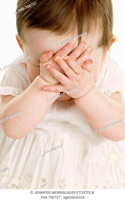 A one-year-old girl wearing a white dress clasps her hands over here face