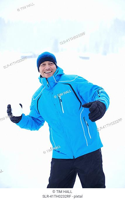 Man throwing snowball outdoors