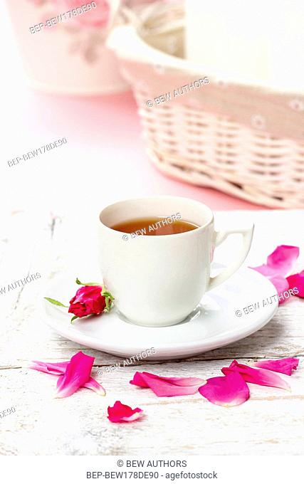 Cup of tea decorated with rose petals in pink table setting