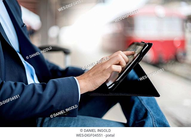 Close-up of businessman at the station using tablet