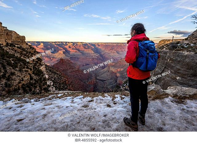 Young woman looking into the gorge of the Grand Canyon, view from the Bright Angel Trail, eroded rock landscape, South Rim, Grand Canyon National Park