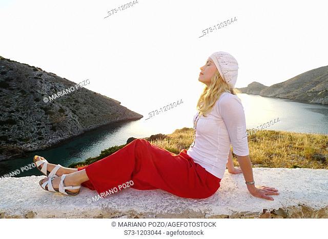 Woman sitting in Galissa beach, Galissa, Syros island,  Greek Island, Cyclades, Greek, Europe