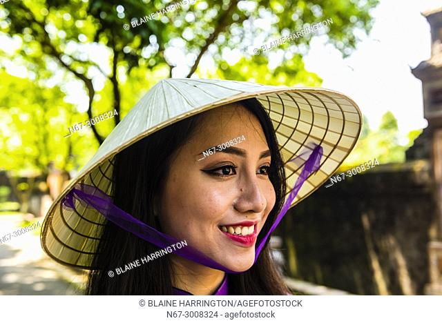 Vietnamese woman in the Imperial City, a walled palace within the citadel of the city of Hu? which is the former imperial capital of Vietnam