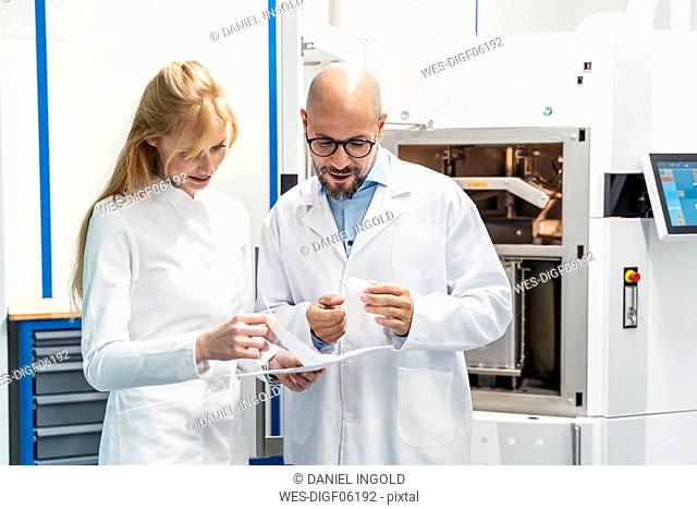Two technicians wearing lab coats discussing plan