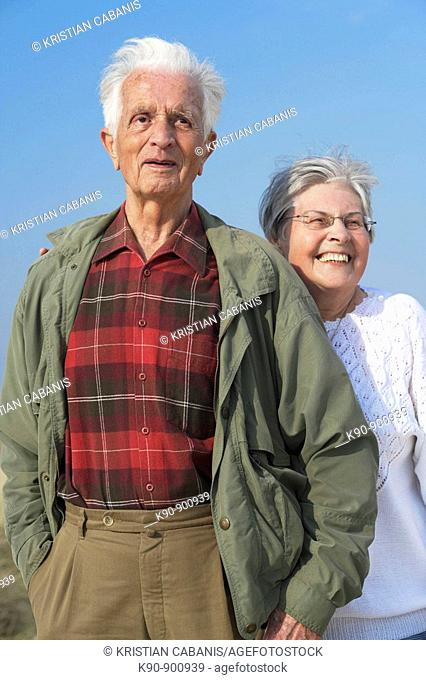 Elderly caucasian couple standing besides each other and looking into the far distance with bright blue sky in the background, Island of Amrum, Northfrisian