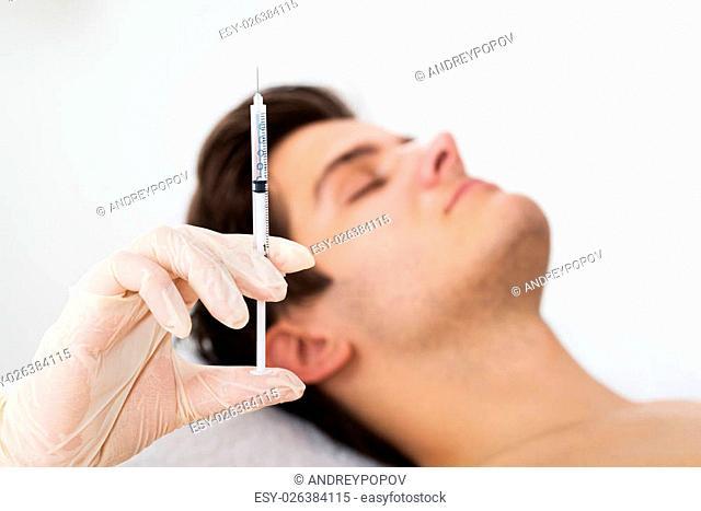 Close-up Of Man Getting Wrinkle Treatment From Female Doctor Holding Syringe