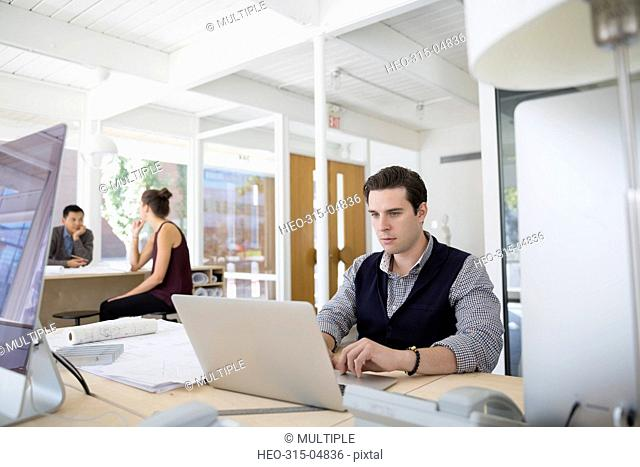 Male architect working at laptop in office