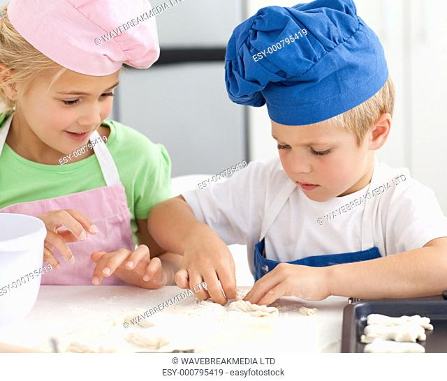 Young brother and sister kneading a dough to make cakes in the kitchen