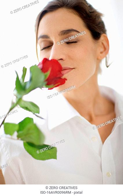 woman breathing in the scent of a rose
