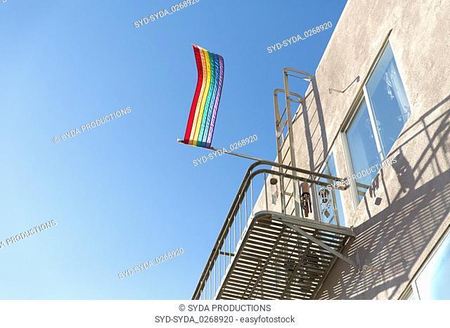 gay pride rainbow flag waving on building balcony