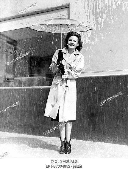 Young woman in a raincoat and umbrella standing in the rain All persons depicted are not longer living and no estate exists Supplier warranties that there will...