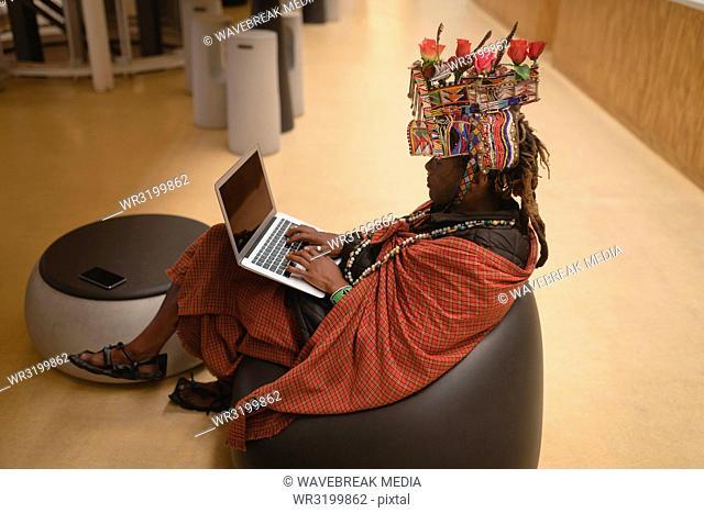 Maasai man in traditional clothing using laptop