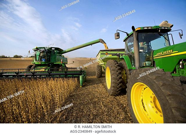 """Agriculture - A John Deere combine harvesting a crop of healthy soybeans in Autumn while unloading into a grain wagon """"on-the-go"""" / near Northland, Minnesota"""