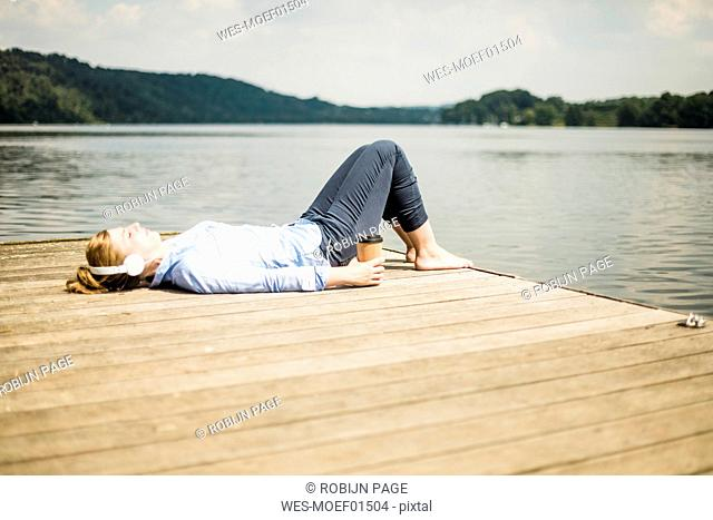 Woman lying on jetty at a lake with headphones and takeaway coffee