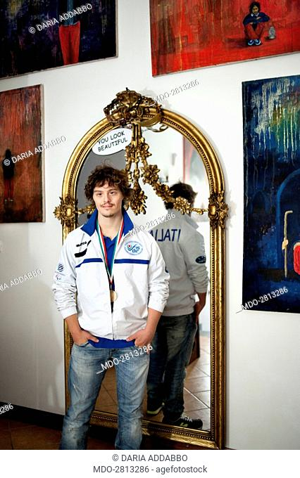 The captain of the paralympic swimming Italian team suffering from Down syndrome Marco Marzocchi posing beside a big mirror for a photocall shooted at home