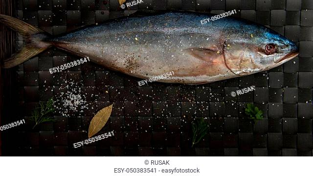 raw tuna fish with salt and spices on black background