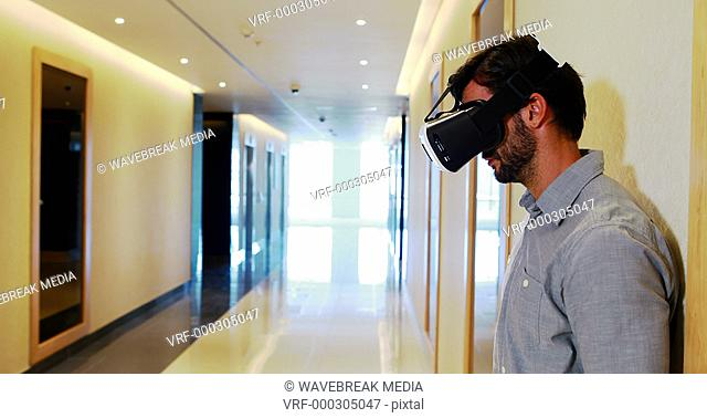 Male executive using virtual reality headset in corridor