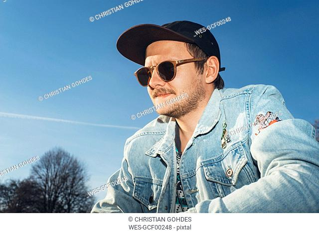 Portrait of a young man under blue sky