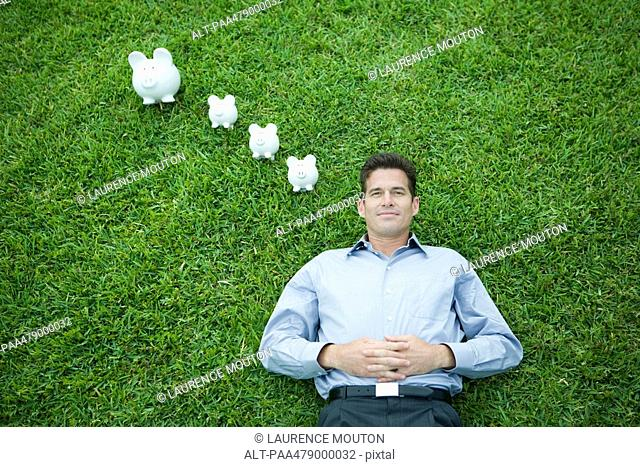 Man lying on grass, smiling, piggy banks by head
