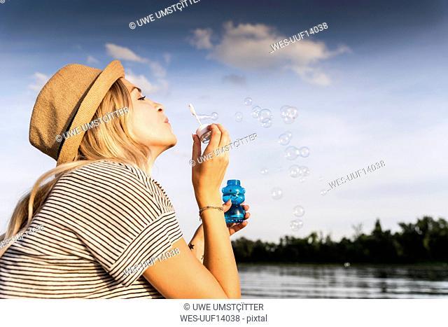 Blond woman blowing soap bubbles
