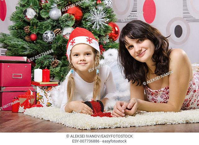 Mum and daughter lie on the five-year rug Christmas tree