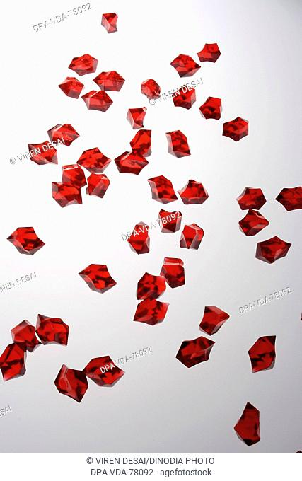 Many red colored acrylic pieces against white background