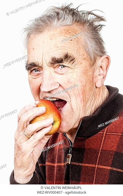 Portrait of senior man eating apple