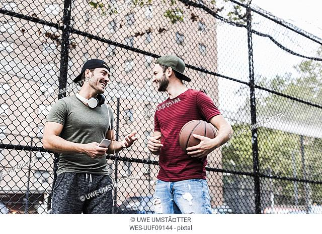 Two smiling friends with basketball outdoors
