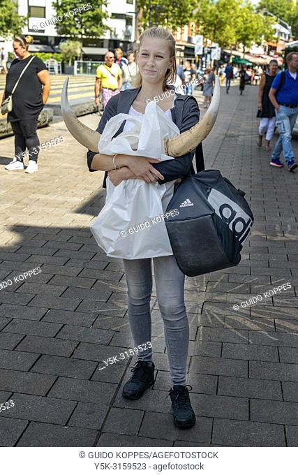 Tilburg, Netherlands. Streetportrait of a young, Polish girl, carrying just purchased bull horns for decorating her living room