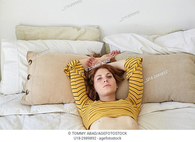 Young redhead woman lying down in bed
