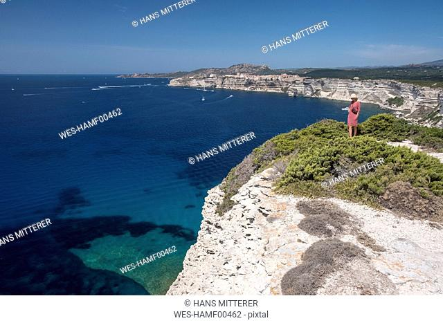 Corsica, Mediterranean coast, woman standing on rocky cliff