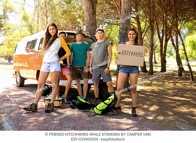 Portrait of friends hitchhiking while standing by camper van