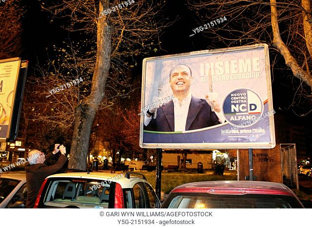 Rome, Italy. 30th March 2014. Political poster for Angelino Alfano's party Nuovo Centrodestra New Centre Right altered with a knife and fork possibly...