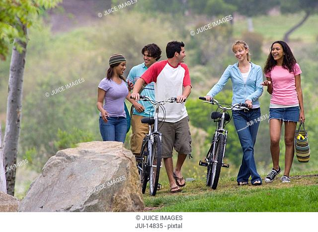 Group of young men and women walking with bicycles outdoors, smiling