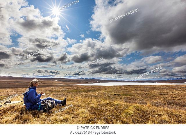 Woman resting on tundra at Etivluk lake, Brooks range mountains, National Petroleum Reserve, Alaska