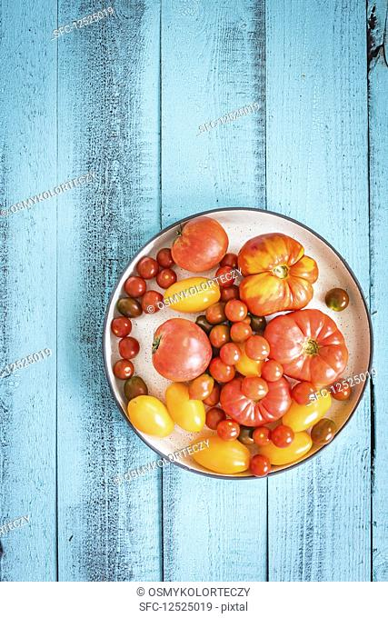 Colourful tomatoes on a blue wood table