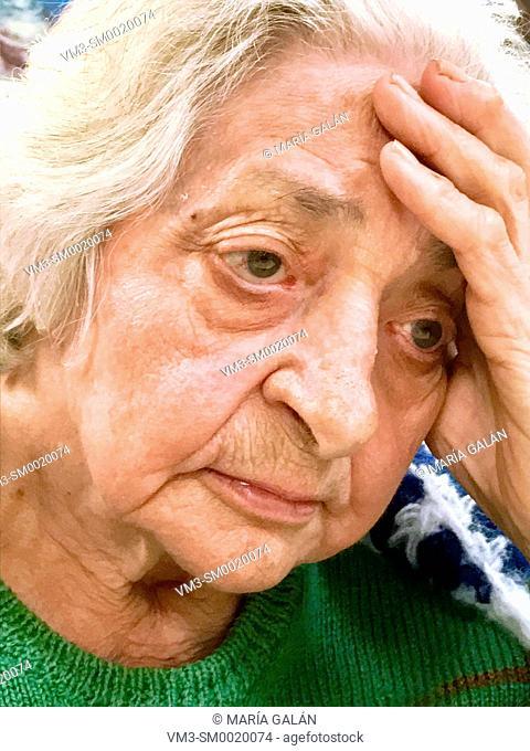 Portrait of pensive old woman. Close view