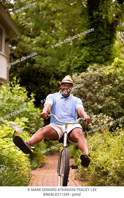 African American man riding bicycle in backyard