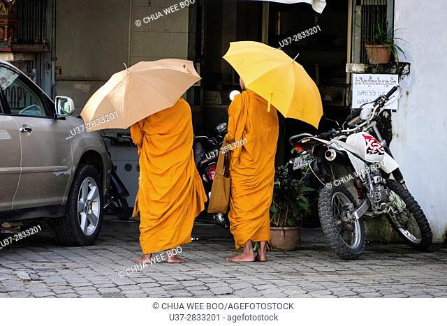 Two Buddhist novices collect alms in Phnom Penh City, Cambodia