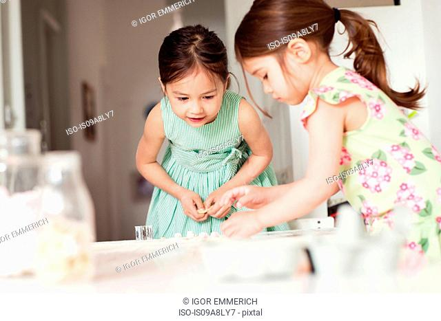 Two young sisters making pastry