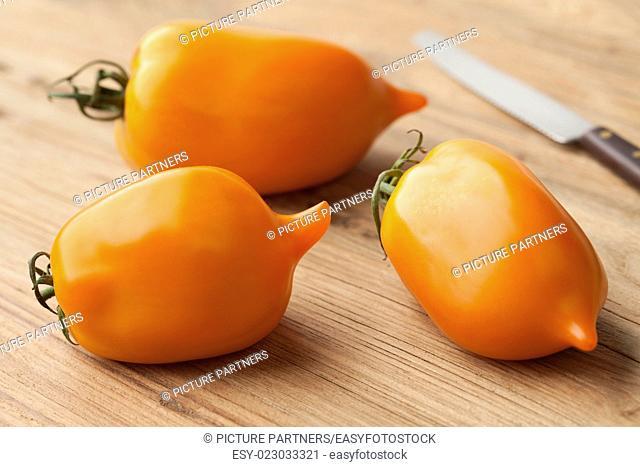 Whole and half fresh orange pepper- tomatoes