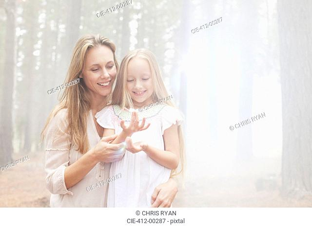 Smiling mother and daughter in sunny woods
