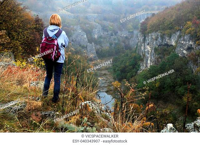 A woman stands on the edge of Emen canyon in Bulgaria on a raw foggy morning in the fall