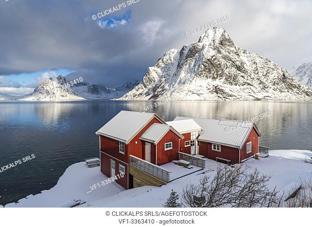 Traditional 'rorbu' houses with Olstinden peak in the background in winter. Reine, Lofoten district, Nordland county, Northern Norway, Norway