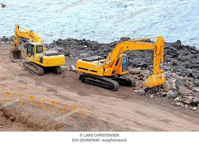 Two orange excavators