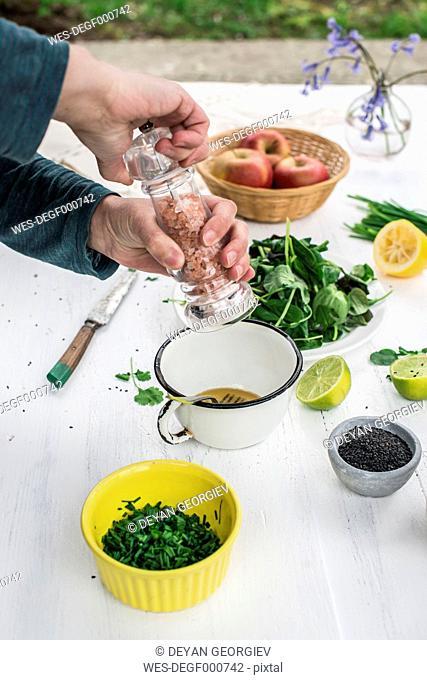 Hand preparing a salad seasoning with salt