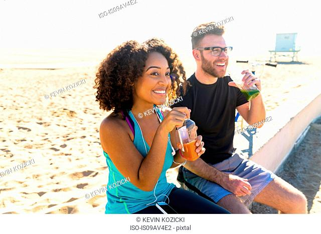 Couple sitting outdoors, drinking fruit juice