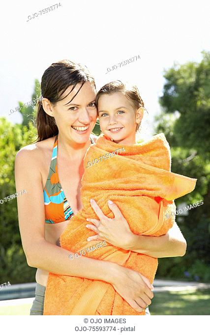 A mother holding her daughter in a towel after a swim