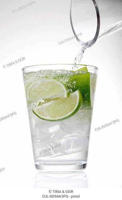 Clear water pouring from jug into drinking glass with lime and ice cubes